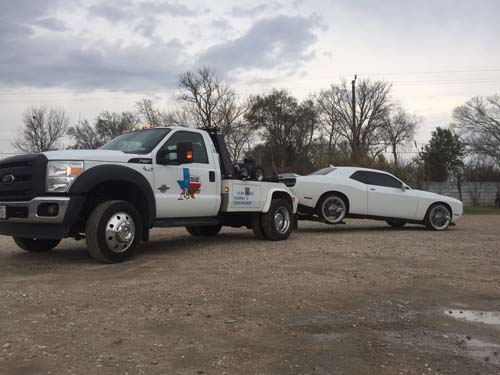 White towing truck towing a white sports car