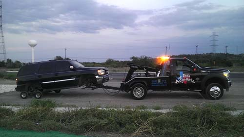 Black truck being pulled by a towing truck