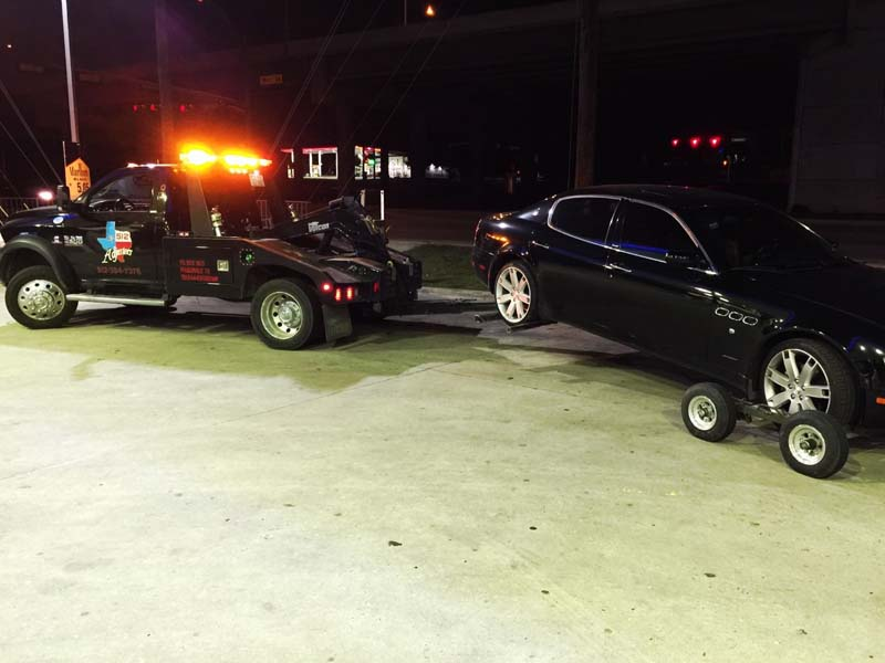 Black car being towed at night