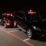 Another black truck being towed at night by a tow truck