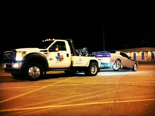 White sports car being towed by a tow truck