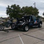 Towing truck towing a black motorcycle